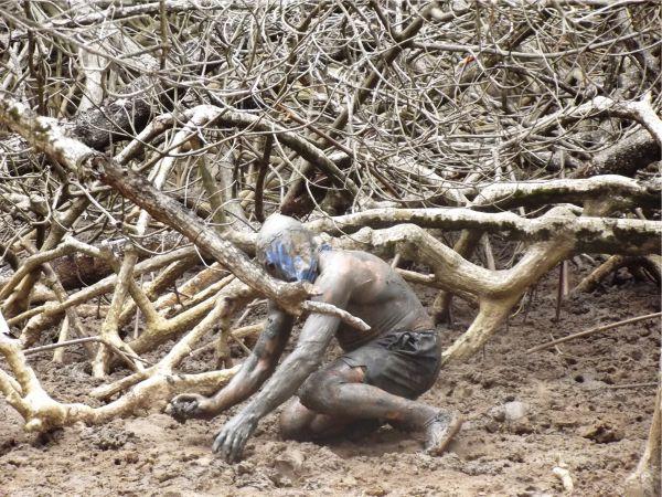 """Homem Lama, uma das atrações do passeio """"pega"""" caranguejo para mostrar aos turistas."""